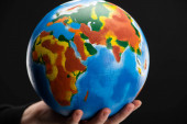 Photo Cropped view of globe in female hand isolated on black, global warming concept