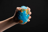 Partial view of woman compressing plasticine globe in hand isolated on black, global warming concept