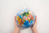 Photo Cropped view of woman holding plastic bag with globe on white, global warming concept