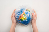 Cropped view of woman holding globe in plastic bag on white background, global warming concept