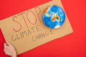 Cropped view of woman holding placard with stop climate change lettering and globe on red, global warming concept