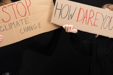 Cropped view of women with placards with stop climate change and how dare you lettering isolated on black, global warming concept stock vector