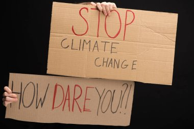 Cropped view of woman with placards with stop climate change and how dare you lettering isolated on black, global warming concept stock vector
