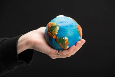 Cropped view of plasticine globe in female hand isolated on black, global warming concept stock vector