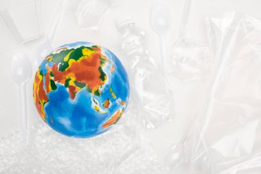 Top view of globe on plastic garbage on white background, global warming concept stock vector