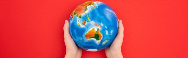 Panoramic view of woman holding globe isolated on red, global warming concept stock vector