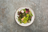 top view of fresh radish salad with greens and avocado on grey concrete surface