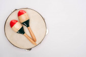 Top view of wooden maracas on tambourine on white background