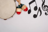Photo Top view of wooden maracas near tambourine and paper cut music notes on white background