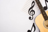 Photo Top view of paper cut notes with music book and acoustic guitar on white background