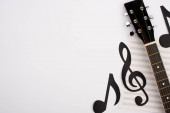 Photo Top view of paper cut notes, music book and acoustic guitar on white background