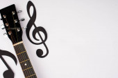 Top view of paper cut music notes and acoustic guitar on white background