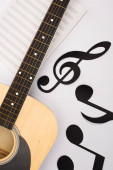 Photo Top view of paper cut notes near music book with acoustic guitar on white background