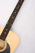 Horní pohled na akustickou kytaru na bílém pozadí