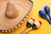 Wooden colorful and blue maracas near sombrero on yellow background