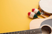 Wooden colorful maracas with tambourine and acoustic guitar on yellow background