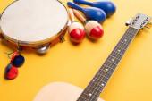Bunte und blaue Maracas aus Holz, Tamburin, Kastagnetten und Akustikgitarre auf gelbem Hintergrund