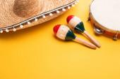 Farbenfrohe Maracas aus Holz, Tamburin und Sombrero auf gelbem Hintergrund