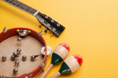 Tambourine near colorful wooden maracas and acoustic guitar on yellow background