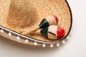 Nahaufnahme von hölzernen Maracas auf Sombrero auf weißem Hintergrund