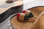 Nahaufnahme von hölzernen Maracas auf Sombrero und akustischer Gitarre auf weißem Hintergrund