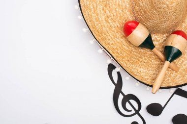 Top view of sombrero and maracas near paper cut music notes on white background