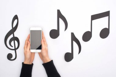 Cropped view of woman holding smartphone near paper cut music notes on white background
