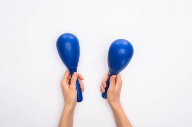 Cropped view of woman holding blue maracas on white background