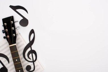 Beyaz arkaplanda kağıt kesme notaları, müzik kitabı ve akustik gitarın üst görünümü