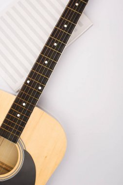 Top view of music book with acoustic guitar on white background