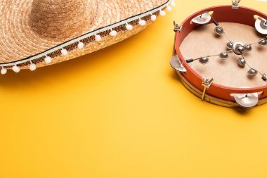Tambourine and mexican sombrero on yellow background