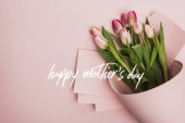 Photo top view of spring tulips wrapped in paper on pink background, happy mothers day illustration