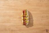 vrchní pohled na lahodný hot dog s nakládanými okurkami, hořčicí a kečupem na dřevěném stole
