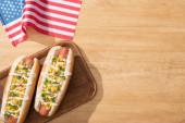 felső kilátás ízletes hot dog kukorica, zöld hagyma és majonéz a fedélzeten közelében amerikai zászló fa asztalon