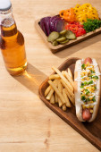Photo delicious hot dog near board with sliced vegetables, beer and french fries on wooden table