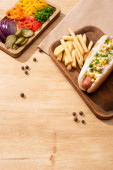 Photo delicious hot dog near board with sliced vegetable and french fries on wooden table