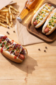 delicious hot dogs near beer and french fries on wooden table