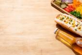 vynikající hot dog s kukuřicí, zelenou cibulí a majonézou v blízkosti láhve piva a stravování se zeleninou na dřevěném stole