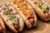 čerstvé různé lahodné hot dogy se zeleninou a omáčkami na dřevěném stole
