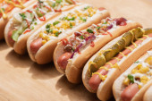 selective focus of fresh various delicious hot dogs with vegetables and sauces on wooden table