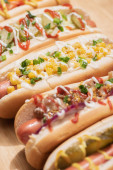Photo selective focus of fresh various delicious hot dogs with vegetables and sauces on wooden table