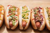 čerstvé různé chutné hot dogy se zeleninou a omáčkami na dřevěném stole