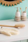 Fotografie Hygienické výrobky na polici v blízkosti masážního kartáče a koupací rukavice v koupelně, koncepce nulového odpadu