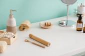 Různé typy hygienických a kosmetických výrobků v blízkosti tyrkysové stěny v koupelně, koncepce nulového odpadu