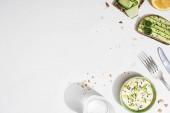 felső kilátás friss uborka pirítós közelében citrom, víz, evőeszközök és joghurt fehér alapon
