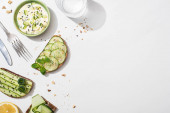Fotografie Draufsicht auf frische Gurken-Toasts in der Nähe von Zitrone, Wasser, Besteck und Joghurt auf weißem Hintergrund