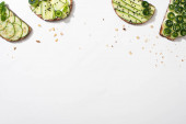 Photo top view of fresh cucumber toasts with seeds, mint and basil leaves on white background