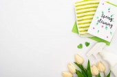 top view of spring tulips and cleaning supplies near spring cleaning card on white background