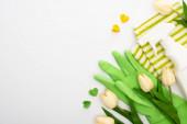pohled shora na jarní tulipány a zelené čistící prostředky a srdce na bílém pozadí