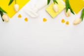 felső nézet tavaszi tulipánok és sárga tisztítószerek szívvel fehér háttér